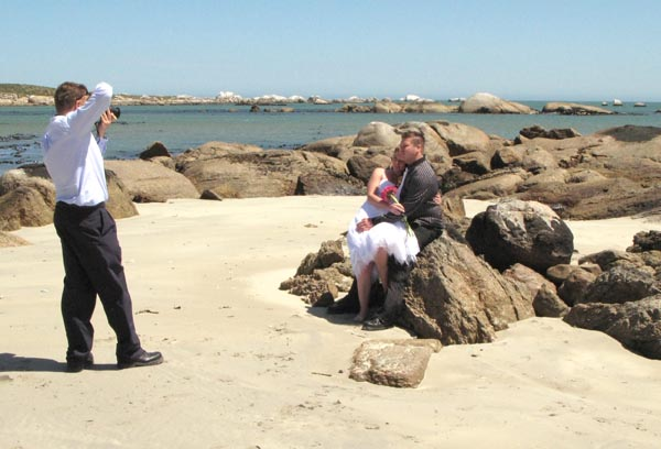 The missing bride and groom having their photographs taken o the beach.