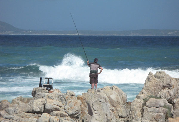 Fishing from the rocks while the family enjoy themselves at the beach about 50 meters away.